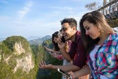 Groupe des jeunes en montagne utilisant le téléphone intelligent de cellules causant l'été asiatique de vacances d'amis en ligne Image stock