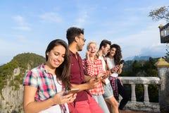 Groupe des jeunes en montagne utilisant le téléphone intelligent de cellules causant l'été asiatique de vacances d'amis en ligne Photos libres de droits