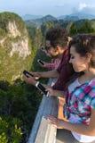 Groupe des jeunes en montagne utilisant le téléphone intelligent de cellules causant l'été asiatique de vacances d'amis en ligne Image libre de droits