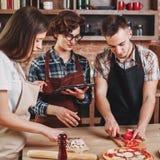 Groupe des jeunes faisant cuire ensemble La femme a lu la recette sur l'étiquette Images stock