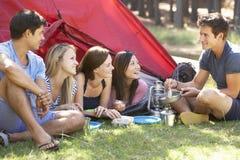 Groupe des jeunes faisant cuire le petit déjeuner des vacances de camping Image libre de droits