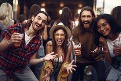 Groupe des jeunes gais avec des boissons ayant l'amusement au concert extérieur photographie stock