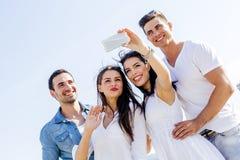 Groupe des jeunes gais et beaux prenant des photos de Th Photos libres de droits