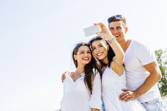 Groupe des jeunes gais et beaux prenant des photos de Th Photos stock