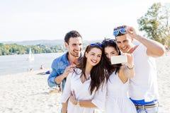 Groupe des jeunes gais et beaux prenant des photos de Th Images stock