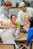 Groupe de personnes gaies grillant avec des cocktails Images stock