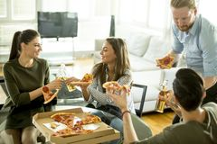 Groupe des jeunes gais mangeant de la pizza dans la chambre et le havi Photo libre de droits