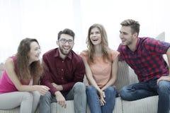 Groupe des jeunes gais s'asseyant sur le divan Photo stock