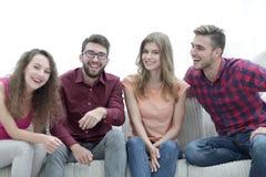 Groupe des jeunes gais s'asseyant sur le divan Image libre de droits