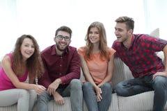 Groupe des jeunes gais s'asseyant sur le divan Images stock