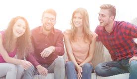 Groupe des jeunes gais s'asseyant sur le divan Image stock