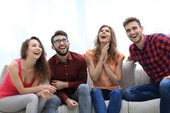 Groupe des jeunes gais s'asseyant sur le divan Photo libre de droits