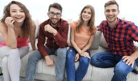 Groupe des jeunes gais s'asseyant sur le divan Photos libres de droits