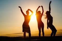 Groupe des jeunes heureux appréciant le coucher du soleil d'été Image stock