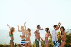 Groupe des jeunes heureux appréciant le coucher du soleil d'été Images libres de droits