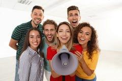 Groupe des jeunes heureux avec le mégaphone images libres de droits