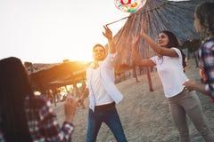 Groupe des jeunes heureux ayant l'amusement sur la plage Image libre de droits