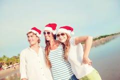 Groupe des jeunes heureux dans des chapeaux de christmass dessus Photographie stock libre de droits
