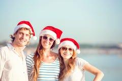 Groupe des jeunes heureux dans des chapeaux de christmass dessus Photos libres de droits
