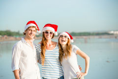 Groupe des jeunes heureux dans des chapeaux de christmass dessus Photographie stock