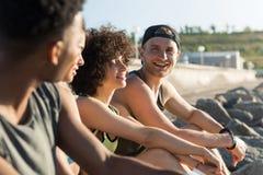 Groupe des jeunes heureux dans les vêtements de sport parlant tout en se reposant Photographie stock libre de droits