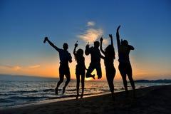 Groupe des jeunes heureux dansant à la plage sur le beau coucher du soleil d'été Photos libres de droits