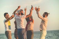 Groupe des jeunes heureux dansant à la plage sur le beau coucher du soleil d'été image libre de droits
