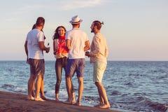 Groupe des jeunes heureux dansant à la plage sur le beau coucher du soleil d'été photo stock