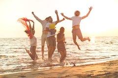 Groupe des jeunes heureux dansant à la plage sur le beau coucher du soleil d'été images libres de droits