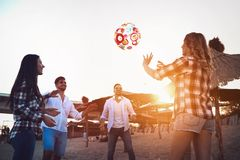 Groupe des jeunes heureux jouant avec la boule sur la plage Photo stock
