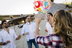 Groupe des jeunes heureux jouant avec la boule sur la plage Image libre de droits