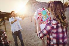 Groupe des jeunes heureux jouant avec la boule sur la plage Photographie stock