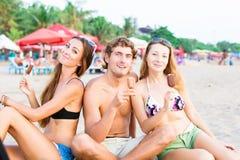 Groupe des jeunes heureux mangeant la crème glacée dessus Photographie stock