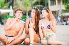 Groupe des jeunes heureux mangeant la crème glacée dessus Image stock