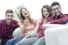 Groupe des jeunes heureux s'asseyant sur le divan Photos libres de droits