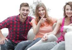 Groupe des jeunes heureux s'asseyant sur le divan Photo libre de droits