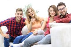 Groupe des jeunes heureux s'asseyant sur le divan Images libres de droits