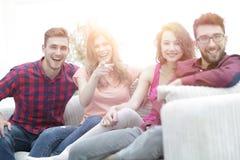 Groupe des jeunes heureux s'asseyant sur le divan Photographie stock libre de droits