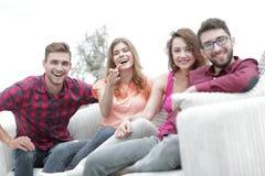 Groupe des jeunes heureux s'asseyant sur le divan Photos stock