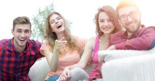 Groupe des jeunes heureux s'asseyant sur le divan Photographie stock