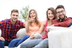 Groupe des jeunes heureux s'asseyant sur le divan Image stock