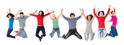 Groupe des jeunes heureux sautant dans le ciel photographie stock libre de droits