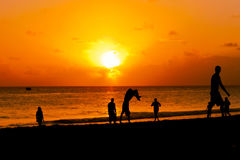 Groupe des jeunes heureux sautant par le coucher du soleil de plage Photos libres de droits