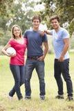 Groupe des jeunes jouant avec la boule de rugby dans la campagne Photo libre de droits