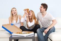 Groupe des jeunes mangeant de la pizza à la maison Photo stock