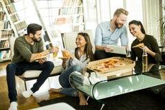 Groupe des jeunes mangeant de la pizza dans la chambre Image libre de droits