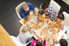 Groupe des jeunes mangeant de la pizza et buvant du cidre photo stock
