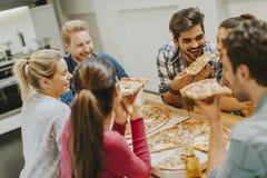 Groupe des jeunes mangeant de la pizza et buvant du cidre images stock