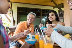 Groupe des jeunes parlant tout en mangeant les amis asiatiques traditionnels de nourriture de soupe de nouilles dinant ensemble Image stock