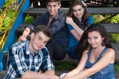 Groupe des jeunes posant à l'extérieur Photo stock